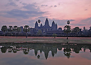 This sunrise shot of Angkor Wat, the world's largest single religious monument was shot in front of the Northern reflecting pond located off the path to the central towers.<br /> <br /> Angkor Wat was built for the king Suryavarman II in the early 12th century as his state temple and capital city.<br /> <br /> It is a massive three-tiered pyramid crowned by five lotus-like towers rising 65 meters from ground level is surrounded by a moat and an exterior wall. All the walls of the temple are covered inside and out with bas-reliefs and carvings. <br /> <br /> The ruins of Angkor, a UNESCO World Heritage Site with temples numbering over 1000, are hidden amongst forests and farmland to the north of the Tonle Sap Lake outside the modern city of Siem Reap, Cambodia. <br />  <br /> It is one of the most awe-inspiring locations I have ever been. From the sunrise to the sunset, there isn't a time of day that is not simply a spectacular time to explore this breathtaking location.