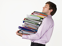Male office worker carrying heavy binders on white background