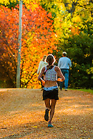 Woman jogging on the Highline Canal path on an Autumn afternoon, Littleton, Colorado USA.