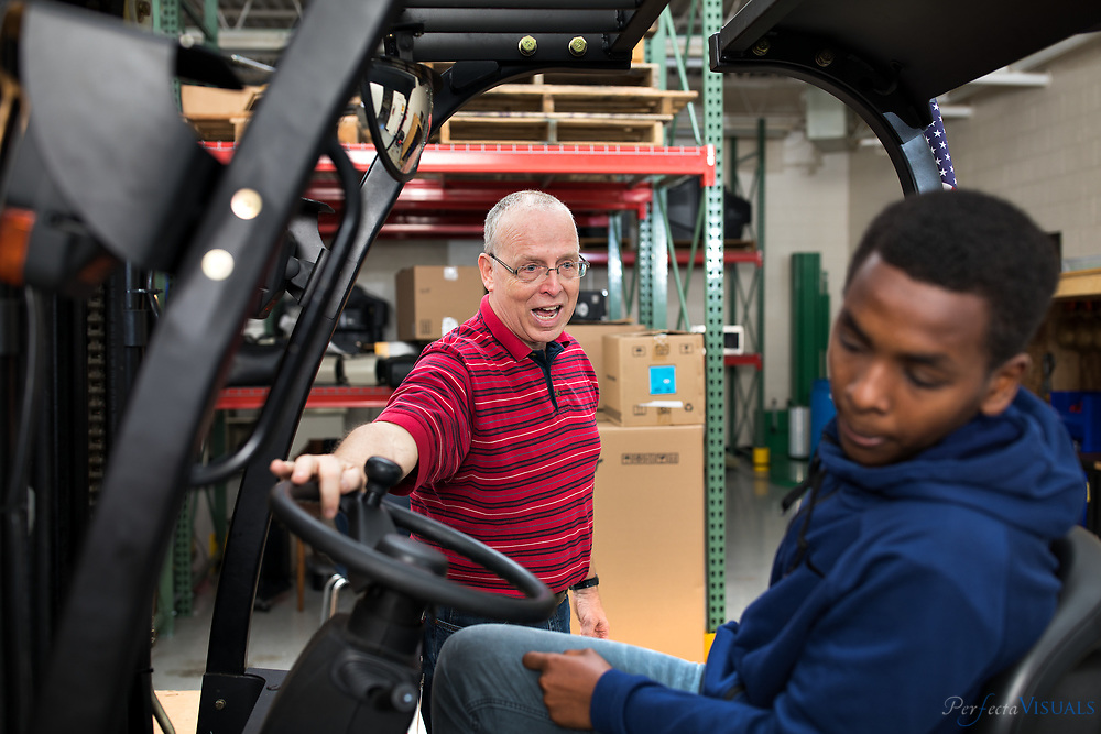 Art Close works with a student while he drives a fork lift  in his Logistics class at Western Guilford High School.<br /> <br /> Western Guilford offers logistics training taught by Art Close. Starting-level classes study warehousing and distribution. That includes the basics of how warehouses function: how to use tools, how to do inventory and so forth. The advanced class, for students who have completed the starting class, covers supply chain management and goes into more depth on topics introduced in the first class. Bob Gantt, the school system&rsquo;s director of career and technical education said that Western Guilford seemed like a good fit for a logistics program because it&rsquo;s close to the airport and certain businesses and distribution centers.<br /> <br /> Photographed, Tuesday, May 8, 2018, in Greensboro, N.C. JERRY WOLFORD and SCOTT MUTHERSBAUGH / Perfecta Visuals