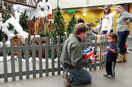 Brian Busse of Applied Imagination (left) gives Dandre Dukes, 2 of Columbus a close look at Thomas the Tank Engine and James the Red Engine before they go on the tracks as the Huntington Holiday Train display setup nears completion at the main branch of the Columbus Metropolitan Library in downtown Columbus., Sunday, November 25, 2012..The trains are setup on Saturday and Sunday and will run through mid-January.
