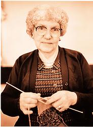 Portrait of elderly woman wearing glasses knitting,