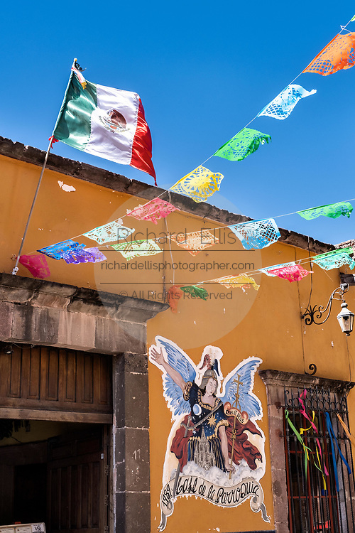 Paper fiesta banners against a clear blue sky decorate Jesus Street in the historic center of San Miguel de Allende, Guanajuato, Mexico.