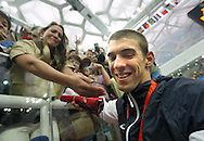 BEIJING, CHINA:  USA's swimmer Michael Phelps is surrounded by photographers as he walks up the stands to hug his mother after he won his final medal in Beijing, China. ©2008 Johnny Crawford