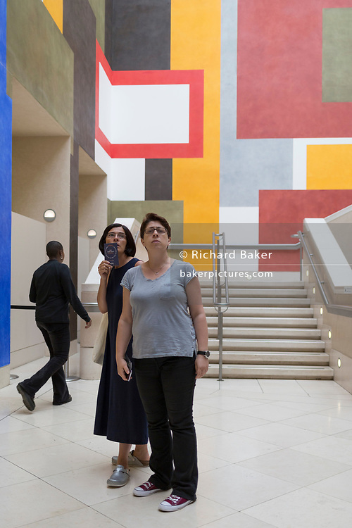 Two women read a wall caption with a background of geometric lines, right-angles and rectangles, on 4th August 2019, at Tate Britain, Millbank, London, England