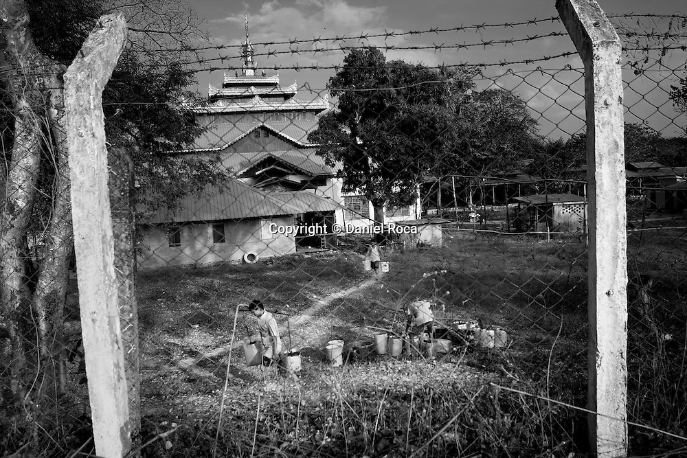 Several young people outside of the pond, fenced with barbed wire. At Dala, Yangon Division, Myanmar, 16th February, 2014.