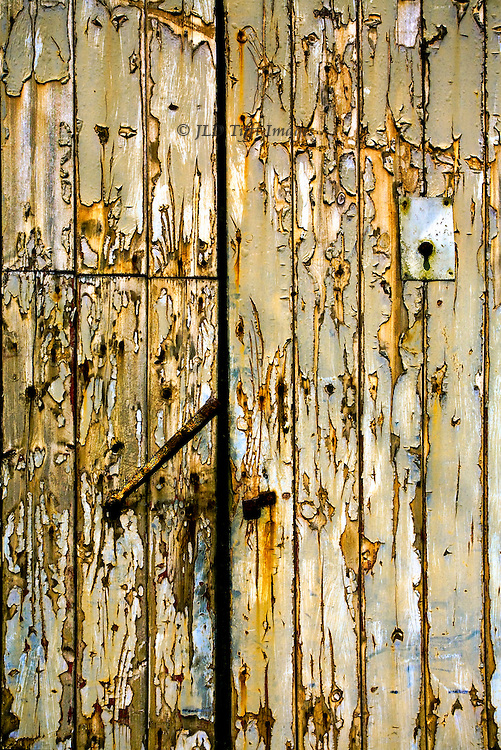 Kettlewell, Upper Wharfedale : wooden barn door with rusted latch and keyhole plate.  Thick peeling paint adds texture.  Beige, orange, and blue colors predominate sue to deliberate saturation of naturally occurring hues.