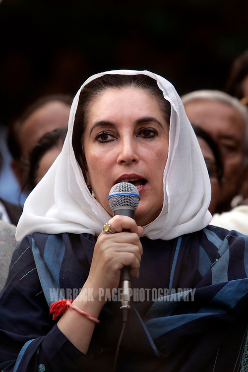 ISLAMABAD, PAKISTAN - NOVEMBER 09:  Former Pakistani Prime Minister, Benazir Bhutto speaks to media after breaking through police lines outside her home on November 9, 2007 in Islamabad, Pakistan. Bhutto was placed under house arrest to prevent her from participating in a planned rally by her political party, the Pakistan People's Party (PPP). Bhutto broke through police lines outside her home to address the media and condemn the move by President Musharraf  and urge him to stick to his commitments of removing his uniform and holding elections. The president declared emergency rule on Saturday, just days before the Supreme Court was to decide on the legitimacy of Musharraf's presidency. (Photo by Warrick Page)