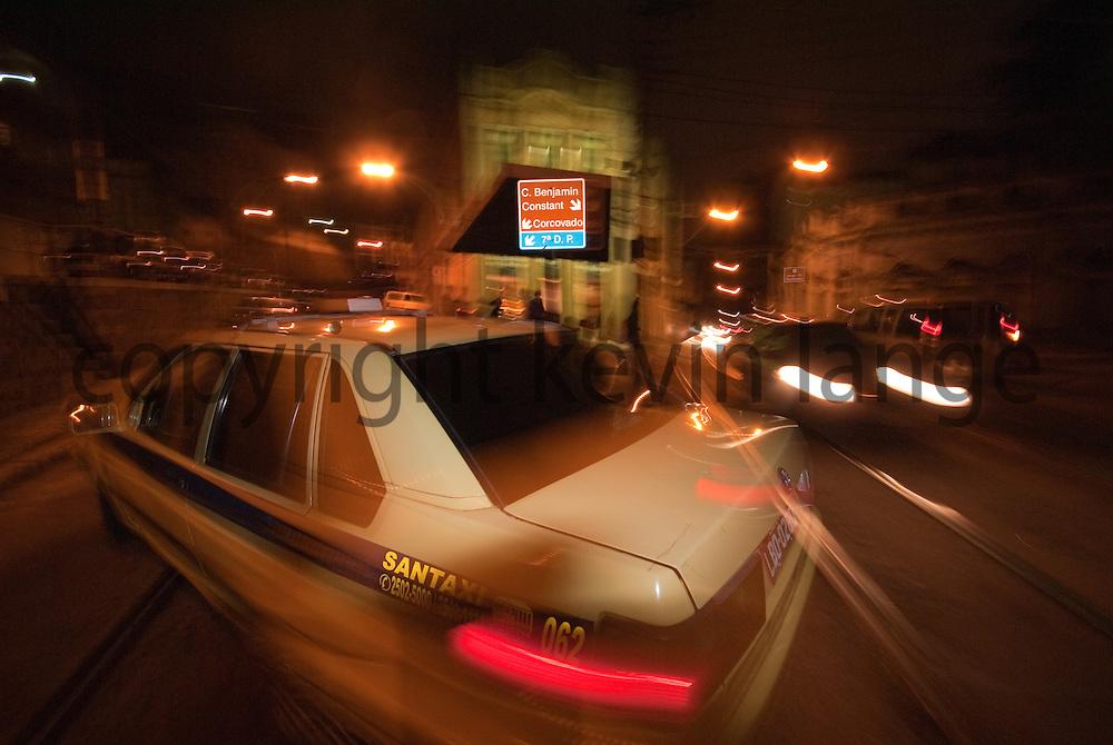 cars pass in the night on a busy corner in the santa teresa neighborhood of rio de janeiro, brazil.
