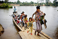 A canoe ferries ethnic minority tribal people across the Sesan River, in Ratanakiri Province, in Cambodiab, on Thursday, April 29, 2010. Villages downstream suffer from flash flooding and poor water quality levels of the Sesan river due five hydropower dams built in Vietnam over a decade ago. Several thousands have been displaced and suffered loss of crops, cattle and fishing.