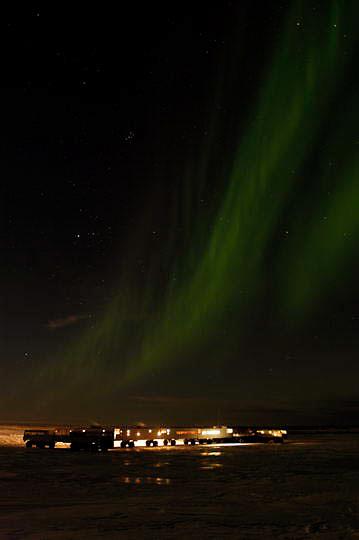 Aurora borealis, also known as Northern Lights dance above Tundra Buggy Lodge. Cape Churchill, Manitoba. Canada.