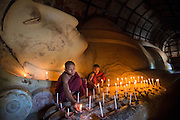 Buddhist monks lighting candles, Bagan, Myanmar