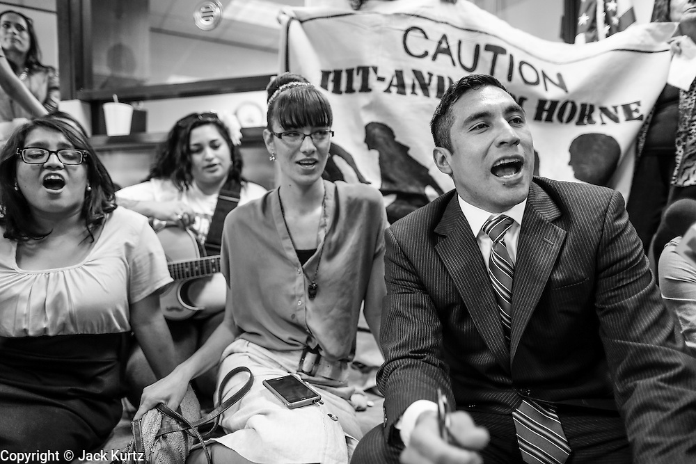 17 OCTOBER 2013 - PHOENIX, AZ: JOSE BETO SOTO, field director of Citizens for a Better Arizona, right, and other protesters chant during a protest in the office of the Arizona Attorney General. About 100 people came to the office of Arizona Attorney General Tom Horne to protest the decision by Horne to sue community colleges in Maricopa County that charge DREAM Act students who are residents of Arizona out of state tuition rather than in state resident tuition. Nearly 10 people were arrested in a planned civil disobedience during the protest.     PHOTO BY JACK KURTZ