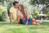 Full length of loving young couple relaxing on grass in park