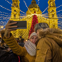 BUDAPEST, HUNGARY - DECEMBER 07:  A couple take a selfie in front of Saint Stephen on December 7, 2017 in Budapest, Hungary. The traditional Christmas market and lights will stay until 31st December 2017.