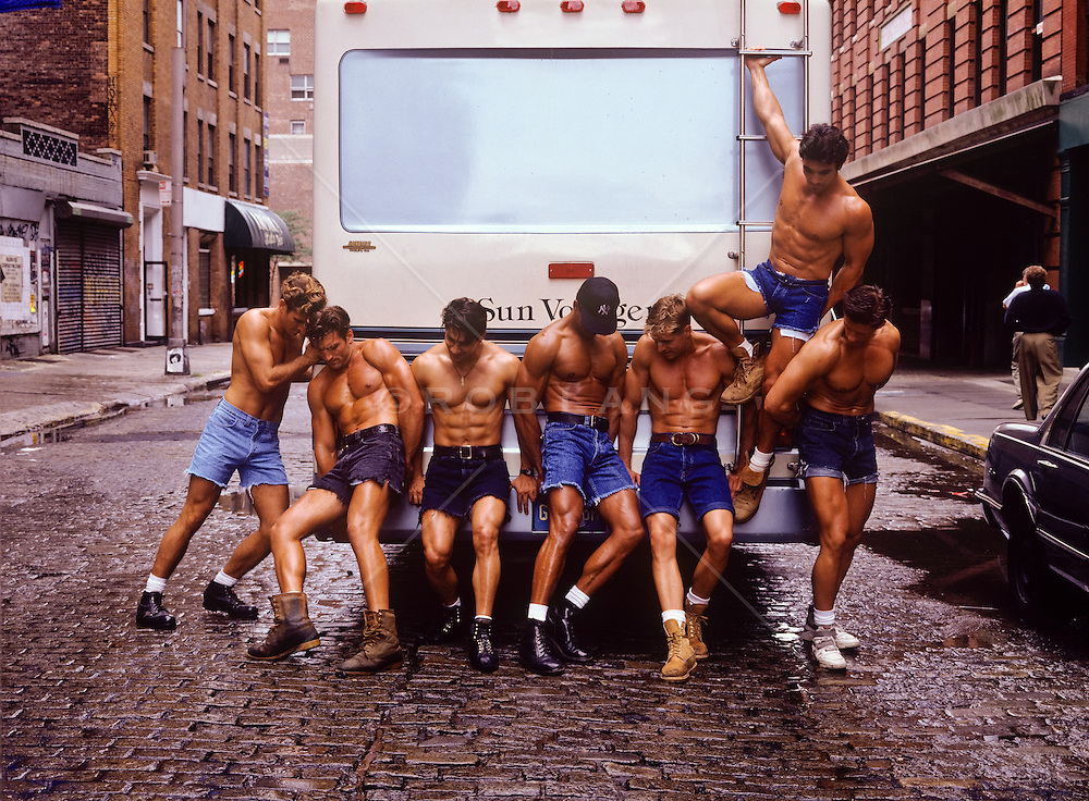 Seven muscular men in cutoff short pushing an RV on the streets of New York City