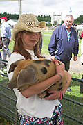 Girl holding an Oxford Sandy Black Piglet at Suffolk Smallholders annual show, Stonham Barns, Suffolk, England, July 2008