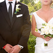 A Bride and Groom pose, showing their flowers from Jayne's Flower Shop, ALS Support Bracelet and gown from Maggie Sottero.