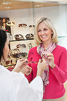 Happy senior woman taking glasses from optician in store