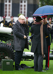 © London News Pictures. 05/11/2013 . London, UK.  Mayor of London BORIS JOHNSON, putting on protecting ear wear before firing a gun salute to launch London Poppy Day at The Honourable Artillery Company in London. The Mayor fired a salute from a 105mm light gun to launch this year's campaign, which aims to raise more than £1million in just one day. Photo credit : Ben Cawthra/LNP