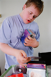 Teenage boy with Downs Syndrome looking through collection of compact disks,
