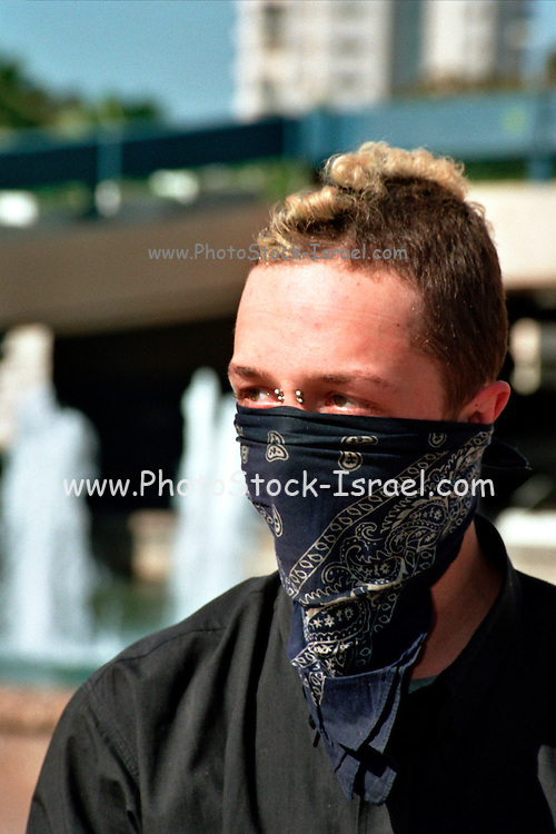 Israel, Tel Aviv, A young man with piercing hiding from the police cameras during a demonstration