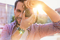Young attractive man standing and holding camera while taking photo with lens flare