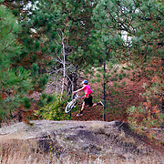 Alex Bardsley get air off a jump in the woods of Missoula, Montana.