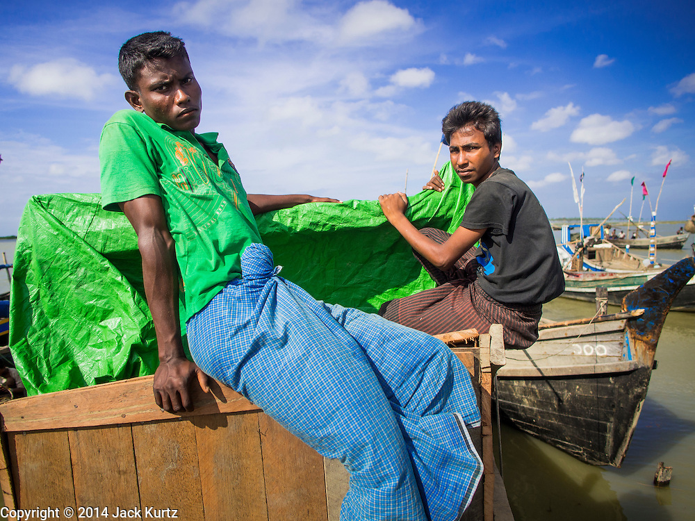 07 NOVEMBER 2014 - SITTWE, RAKHINE, MYANMAR:  A Rohingya men on a boat in the port of a Rohingya IDP camp near Sittwe. The government of Myanmar has forced more than 140,000 Rohingya Muslims who used to live in Sittwe, Myanmar, into squalid Internal Displaced Person (IDP) camps. The forced relocation took place in 2012 after sectarian violence devastated Rohingya communities in Sittwe and left hundreds dead. None of the camps have electricity and some have been denied access to regular rations for nine months. Conditions for the Rohingya in the camps have fueled an exodus of Rohingya refugees to Malaysia and Thailand. Tens of thousands have put to sea in rickety boats hoping to land in Malaysia but sometimes landing in Thailand. The exodus has fueled the boat building boom on the waterfront near the camps. Authorities expect the pace of refugees fleeing Myanmar to accelerate during the cool season, December through February, when there are fewer storms in the Andaman Sea and Bay of Bengal.  PHOTO BY JACK KURTZ