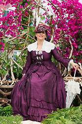© Licensed to London News Pictures. 19/05/2014. London, England. Woman dressed in old-fashioned dress poses in front of flowers. Press Day at the RHS Chelsea Flower Show. On Tuesday, 20 May 2014 the flower show will open its doors to the public.  Photo credit: Bettina Strenske/LNP