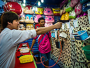 24 NOVEMBER 2015 - BANGKOK, THAILAND:  A young man shoots a bb gun at an arcade shooting gallery at the Wat Saket temple fair. Wat Saket is on a man-made hill in the historic section of Bangkok. The temple has golden spire that is 260 feet high which was the highest point in Bangkok for more than 100 years. The temple construction began in the 1800s in the reign of King Rama III and was completed in the reign of King Rama IV. The annual temple fair is held on the 12th lunar month, for nine days around the November full moon. During the fair a red cloth (reminiscent of a monk's robe) is placed around the Golden Mount while the temple grounds hosts Thai traditional theatre, food stalls and traditional shows.       PHOTO BY JACK KURTZ