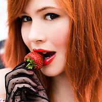 portrait of redhead biting on strawberry