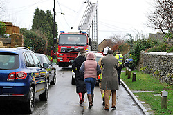© Licensed to London News Pictures. Date 4 January 2014. Woodstock, Oxfordshire. Fire crew escort people to the scene of the fire. Body  a woman (the householder) in her late 70's, has been found in a fire damaged house that has partially collapsed in Green Lane Woodstock. Photo credit : MarkHemsworth/LNP