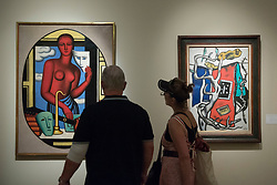 "© Licensed to London News Pictures. 29/06/2017. London, UK.  Members of the public view (L to R) ""Les Masques"", 1928, by Jean Metzinger and ""Le Tapis Rouge Dans Le Paysage"", 1952, by Fernand Léger during a visit to Masterpiece London, a leading art fair held in the grounds of the Royal Hospital Chelsea.  The fair brings together 150 international exhibitors presenting works from antiquity to the present day and runs 29 June to 5 July 2017.  Photo credit : Stephen Chung/LNP"