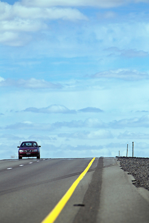 JEROME A. POLLOS/Press..A motorist travels south on Highway 95 near Worley as clouds fill the sky Wednesday.