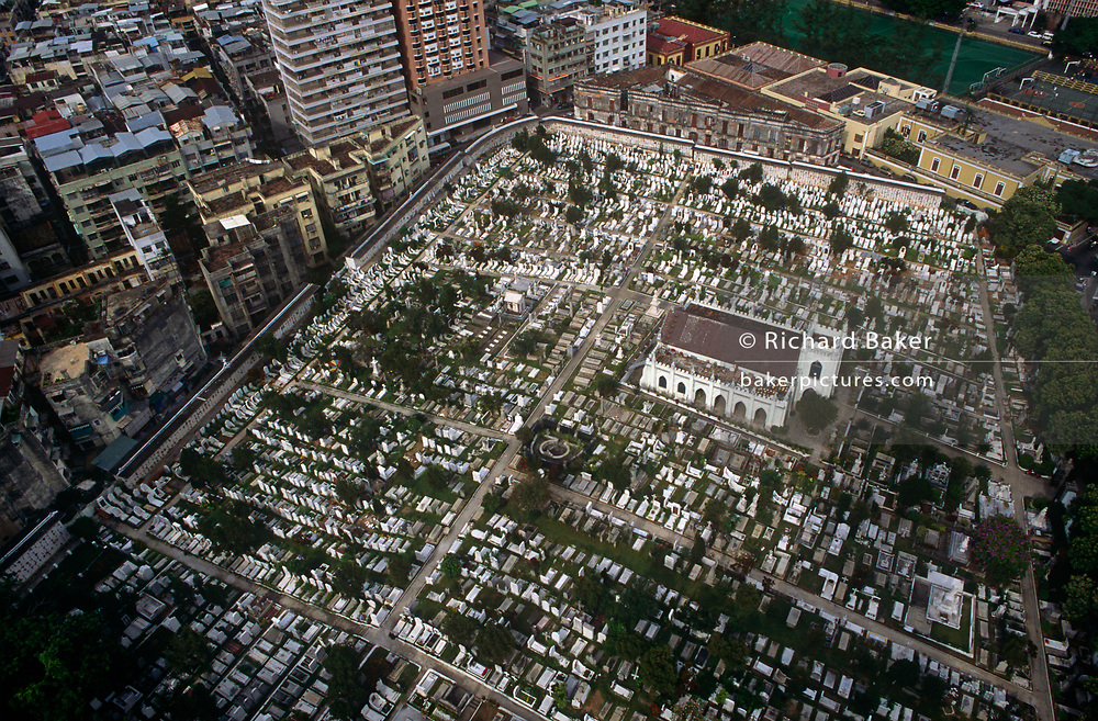 An aerial view overlooking the Cemiterio de São Miguel Arcanjo (Saint Miguel Catholic Cemetery) the ex-Portuguese colony of Macau's Chinese Christian cemetery of San Miguel, on 10th August 1994, in Macau, China. The cemetery is located right in the middle of Macao island, on Estrada do Cemiterio and host the graves of the old Dutch and Portuguese colonials that helped shape Macau, now one of the world's most densely-populated city. The Macau Special Administrative Region is one of the two special administrative regions of the People's Republic of China (PRC), along with Hong Kong. Administered by Portugal until 1999, it was the oldest European colony in China, dating back to the 16th century. The administrative power over Macau was transferred to the People's Republic of China (PRC) in 1999, 2 years after Hong Kong's own handover.