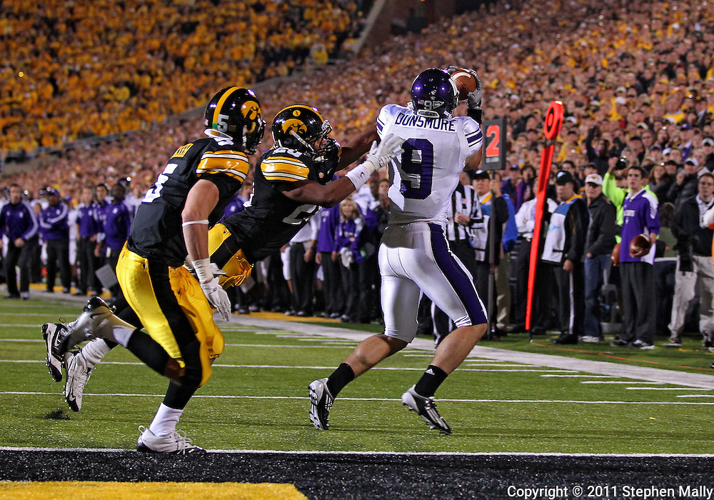 October 15, 2011: Northwestern Wildcats tight end Drake Dunsmore (9) pulls in a 18 yard touchdown pass as Iowa Hawkeyes linebacker Christian Kirksey (20) and Iowa Hawkeyes defensive back Tanner Miller (5) defend during the second half of the NCAA football game between the Northwestern Wildcats and the Iowa Hawkeyes at Kinnick Stadium in Iowa City, Iowa on Saturday, October 15, 2011. Iowa defeated Northwestern 41-31.