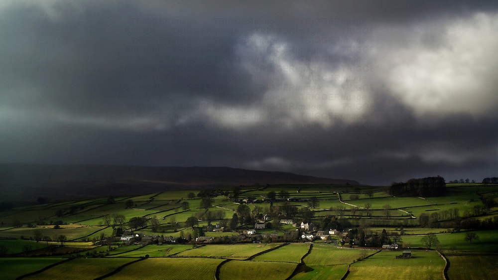 Dark storm clouds above green fields and small villages in England