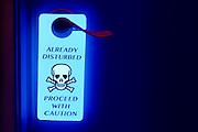 "A glowing ""Already Disturbed"" sign hangs from a door knob.Black light"