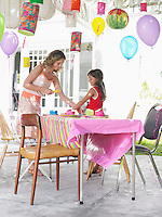 Mother and daughter (7-9) laying table for birthday party side view