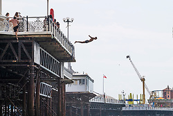 © Licensed to London News Pictures. 09/08/2020. Brighton, UK. Members of the public can be seen jumping of Brighton Palace Pier in to the sea in Brighton And Hove on the hottest weekend of the year so far with temperatures going well in the 30C's in the South Coast. Photo credit: Hugo Michiels/LNP
