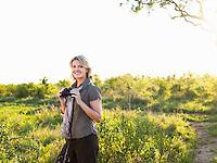 Portrait of adult woman holding binoculars