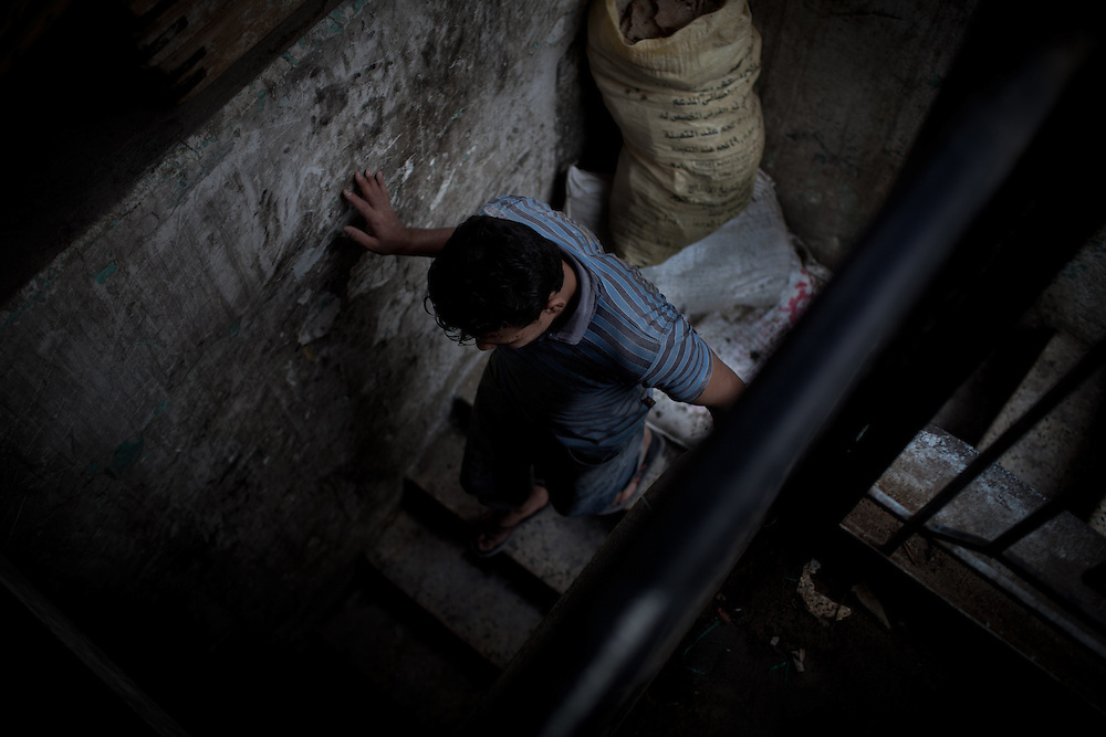 Ammar Esam, 20, a baker from upper Egypt runs down the stairs of the bakery in the Abbassia neighborhood of Cairo Egypt.