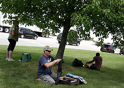 June 21, 2017 - Flynt, Michigan, U.S. - MICHAEL DAVIDSON of Fenton, goes through his suitcase under the shade of a tree with other passengers waiting for clearance to go back inside Bishop International Airport. A police officer was stabbed at the airport earlier in the day and the airport evacuated. Davidson has been waiting to go to Florida for a funeral since 11 am. (Credit Image: © Detroit Free Press via ZUMA Wire)