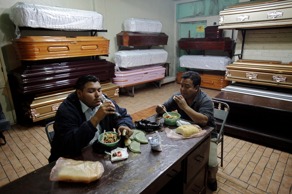 """""""Valle del Sol"""" funeral home employees, Gabriel, left and Tono, right,  eat chowmein sandwiches during a break  from their night shift, Guatemala City, Saturday, Aug 29,  2009. In Guatemala, funeral homes provide services that go beyond preparing bodies and organizing a wake. Guatemala's constant streak of murders _17-a-day in a city of two million_ and death by common illneses provide a steady flow of customers. In a completely unregulated industry, improvised morticians embalm corpses in the back of auto repair shops and rush to crime scenes to gather information that will allow them to locate, notify and make a sales pitch to the bereaved relatives.(AP Photo/Rodrigo Abd)"""