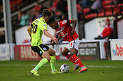 Walsall defender, Rico Henry takes on Brighton striker, Solomon March during the Capital One Cup match between Walsall and Brighton and Hove Albion at the Banks's Stadium, Walsall, England on 25 August 2015.