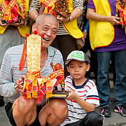 Grandfather and Grandson display spirit tablet of Xuantian and wooden effigy of San Tai Tz, Tainan City, Taiwan
