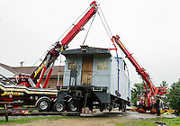 John Dapergolas of John's and John Kemp of Coady's secure Pitman's Freight Room's caboose as they lift it onto its new set of tracks Wednesday afternoon.  (Karen Bobotas/for the Laconia Daily Sun)