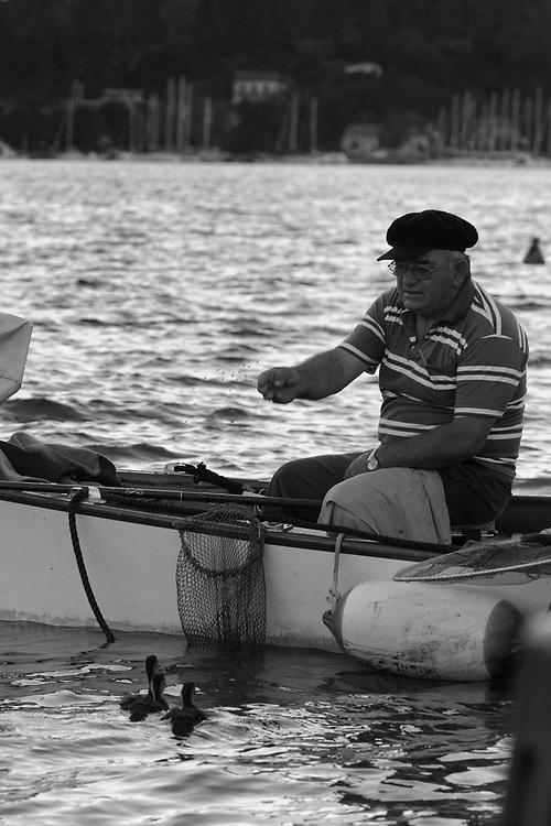 Man feeding birds in Fiumaretta Italy.