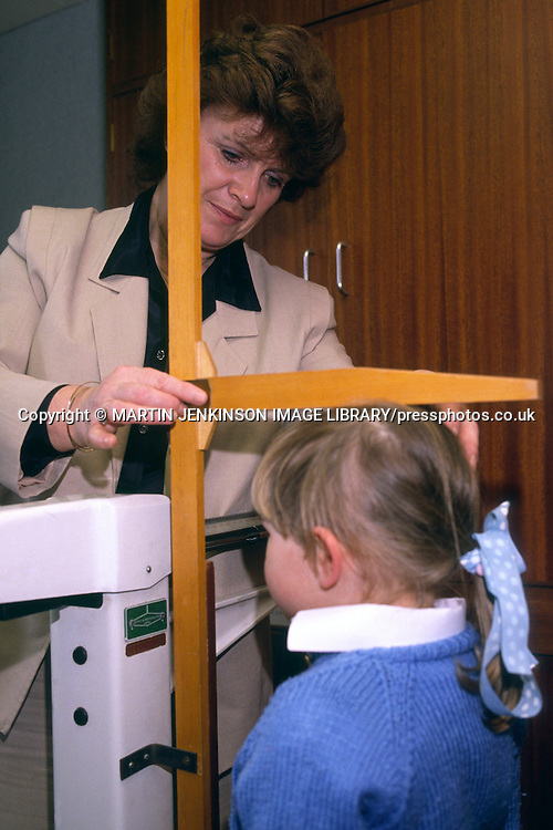 School Nurse measuring the height of a primary school pupil ....
